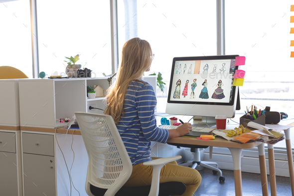 Young Female Fashion Designer Using Graphic Tablet While Working At Desk Stock Photo By Wavebreakmedia