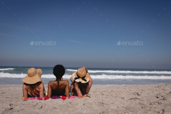 Young women lying and relaxing on a blanket at beach in front of the sea under the sunshine - Stock Photo - Images
