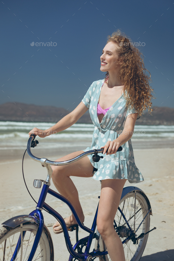 Side view of Caucasian woman riding bicycle at beach on a sunny day.She is smiling - Stock Photo - Images