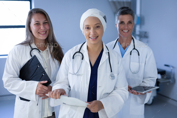 Female doctors standing in the hospital with stethoscope around the neck while holding folder - Stock Photo - Images