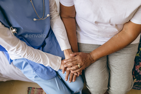 Female doctor holding hand of senior African-american patient at retirement home - Stock Photo - Images