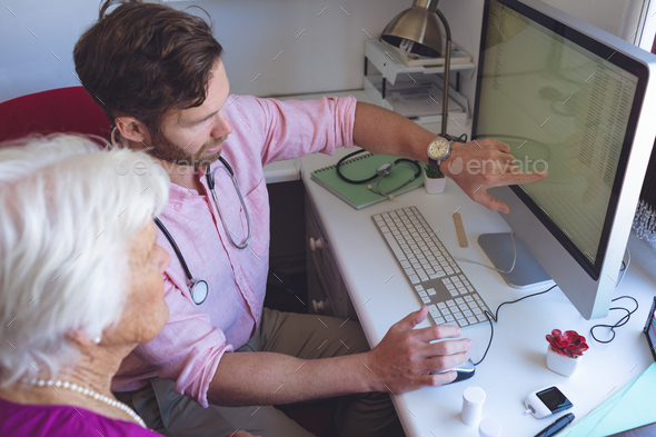 Male doctor showing medical reports on computer to a female senior patient in a clinic room - Stock Photo - Images