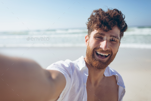 Man taking a selfie standing and at beach - Stock Photo - Images