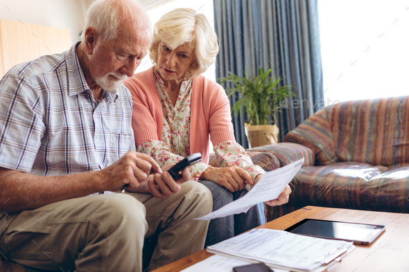 Front view of active Senior Caucasian couple calculating bill while sitting at retirement home - Stock Photo - Images