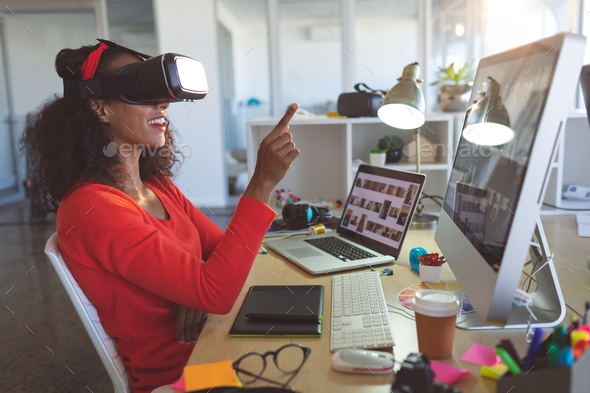 Female graphic designer using virtual reality headset at desk in a modern office - Stock Photo - Images
