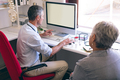 Male doctor discussing over computer with senior woman at retirement home clinic - PhotoDune Item for Sale