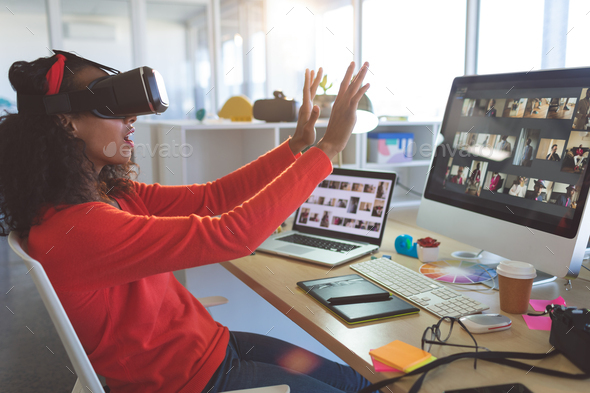 Young female graphic designer using virtual reality headset at desk in a modern office - Stock Photo - Images