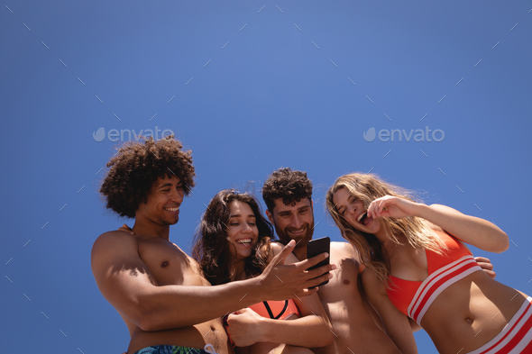 Happy group of friends reviewing photos on mobile phone at beach in the sunshine - Stock Photo - Images
