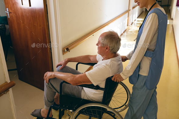 Female nurse pushing disabled senior male patient sitting in wheelchair at retirement home - Stock Photo - Images