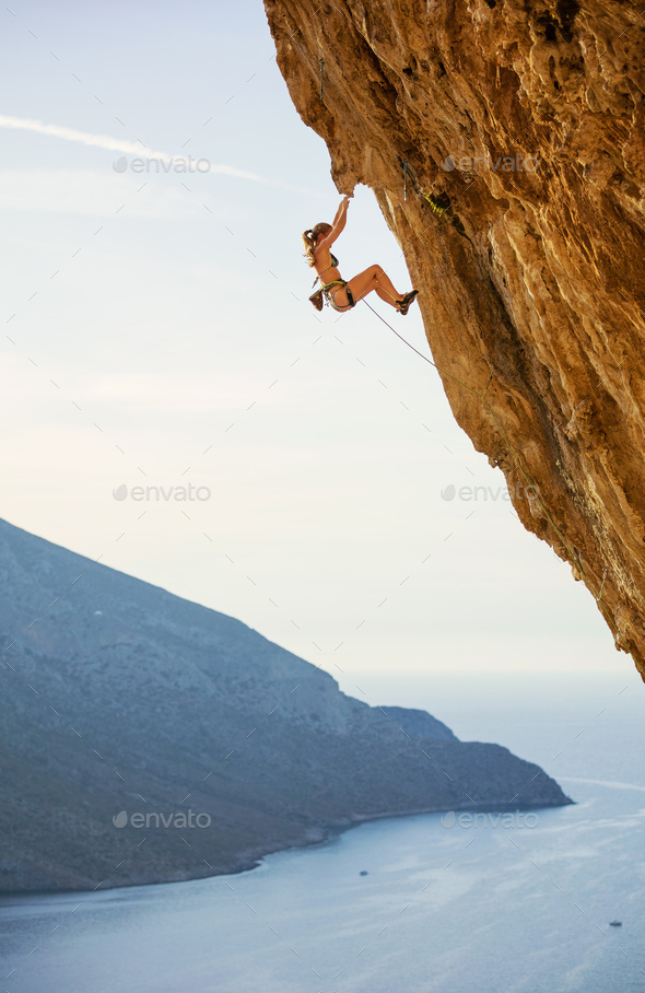 Young woman in bikini climbing challenging route  - Stock Photo - Images
