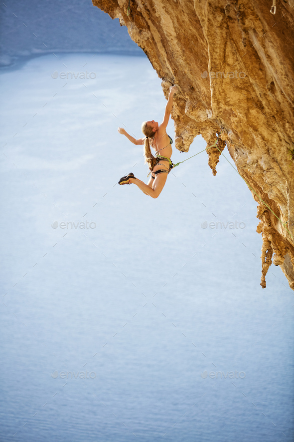 Young female rock climber in bikini hanging with one hand  - Stock Photo - Images