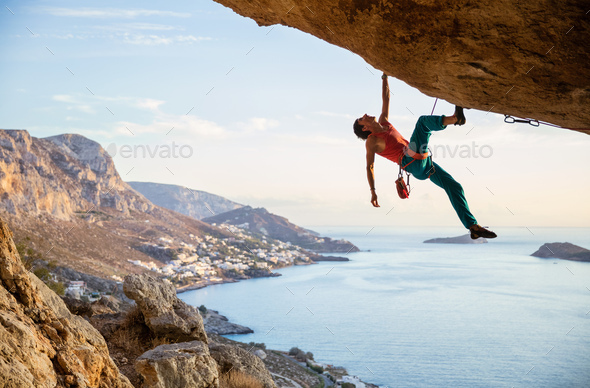 Caucasian man climbing challenging route in cave at sunset - Stock Photo - Images
