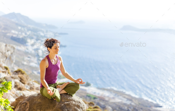Caucasian young woman practicing yoga while sitting in lotus pose - Stock Photo - Images