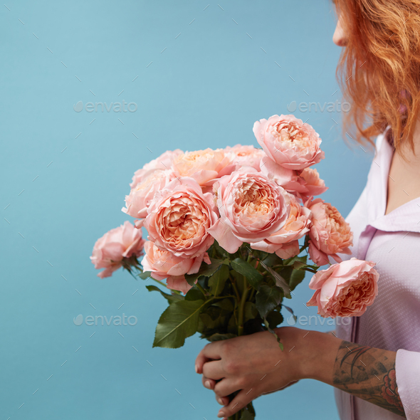 Gentle pink roses in the hands of a girl with a tattoo on a blue background with copy space for text - Stock Photo - Images