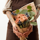 Close-up of greeting bouquet from fresh roses, eryngium and green leaves a in a female's hands - PhotoDune Item for Sale