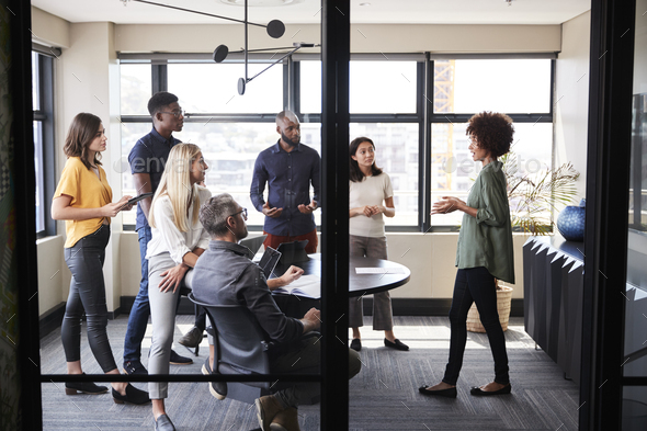 Creative business team listening to their female colleague presenting at a brainstorm meeting - Stock Photo - Images