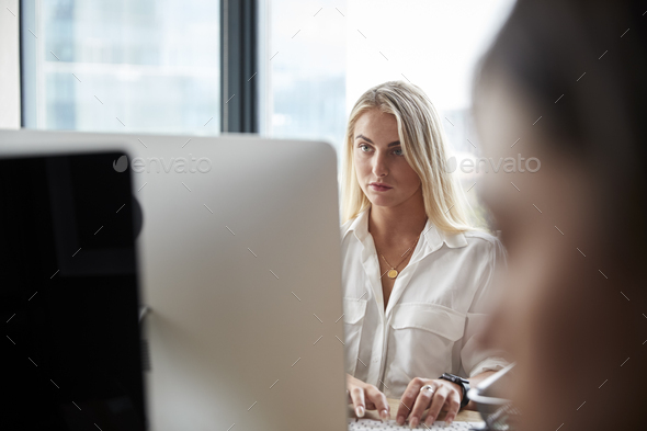Young white blonde woman working at a computer in a busy creative office, close up - Stock Photo - Images