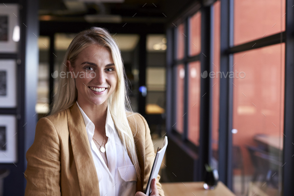 Millennial white blonde businesswoman smiling to camera by the window in an office, close up - Stock Photo - Images