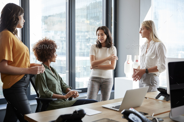 Four female colleagues in discussion at a desk in a creative office, three quarter length - Stock Photo - Images