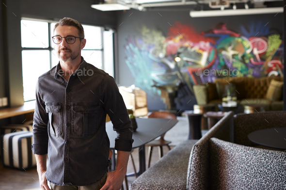 Middle aged white male creative standing in casual office canteen, cafe area looking to camera - Stock Photo - Images