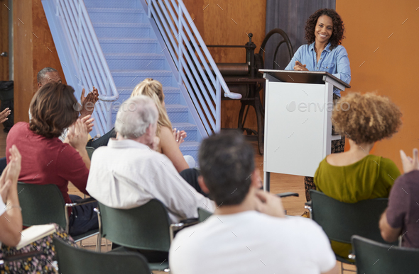 Woman At Podium Chairing Neighborhood Meeting In Community Centre - Stock Photo - Images