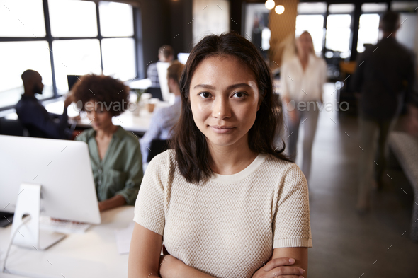 Millennial Asian female creative standing in a busy casual office, smiling to camera - Stock Photo - Images