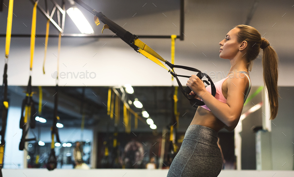 Young woman performing TRX training in gym, copy space - Stock Photo - Images