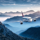 Airplane is flying over mountains in fog at colorful sunset - PhotoDune Item for Sale
