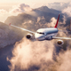 Airplane is flying over mountains and low clouds at sunset - PhotoDune Item for Sale