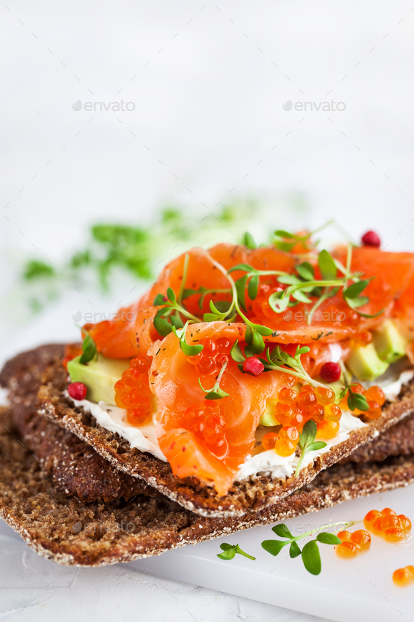 Salted salmon, red caviar, avocado and cream cheese rye crisp to - Stock Photo - Images