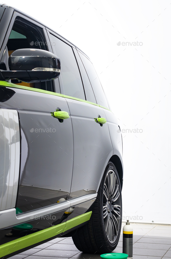 Car in applying green protective tape before polishing - Stock Photo - Images