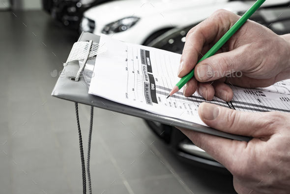Mechanic writing to the clipboard at workshop warehouse - Stock Photo - Images