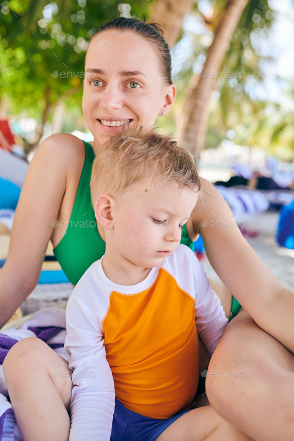 Toddler boy at tropical beach with mother - Stock Photo - Images