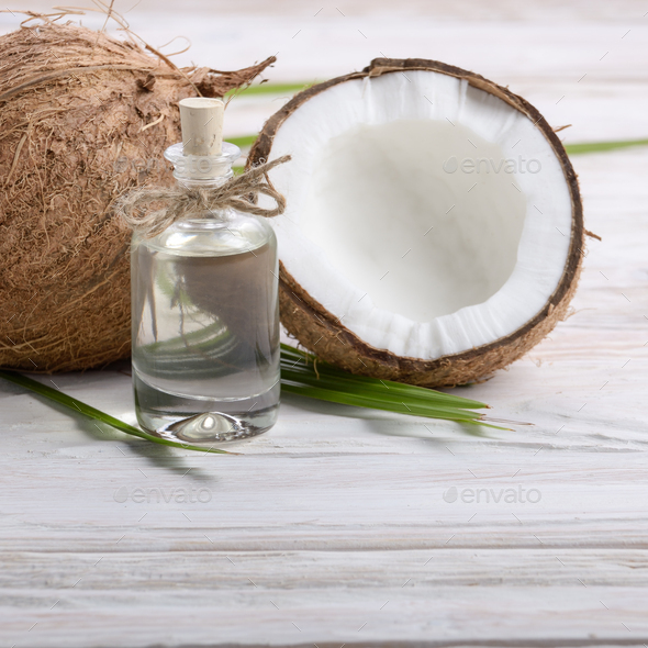 Coconut oil in glass jar and shell pieces on white wooden table - Stock Photo - Images