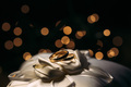 Golden wedding rings on silk cloth with bokeh lights in background - PhotoDune Item for Sale