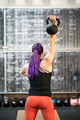 Rear view of a young woman swinging a kettlebell - PhotoDune Item for Sale