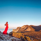 Young beautiful woman in red dress looking to mountains sea - PhotoDune Item for Sale