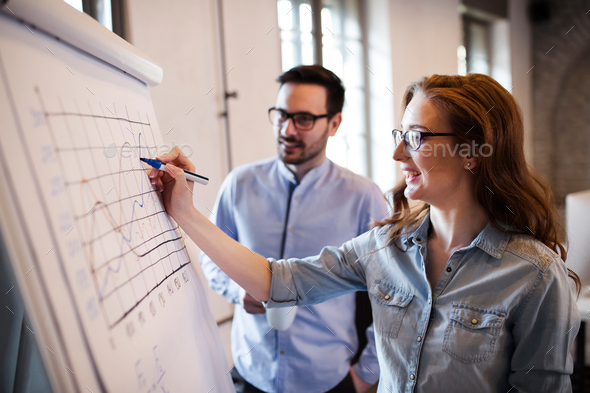 Portrait of architects discussing and drawing on board - Stock Photo - Images