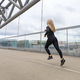 Fast running sporty woman in black workout outfit in modern city environment - PhotoDune Item for Sale