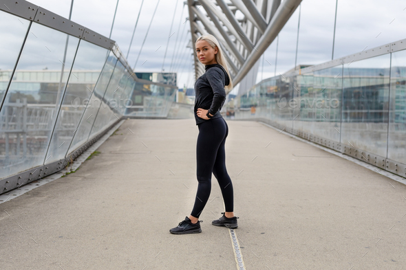 Fit Female Beauty in Black Workout Wear Standing At Modern Bridge In City - Stock Photo - Images