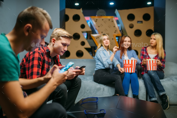 Group of teenagers waiting for the film in cinema - Stock Photo - Images