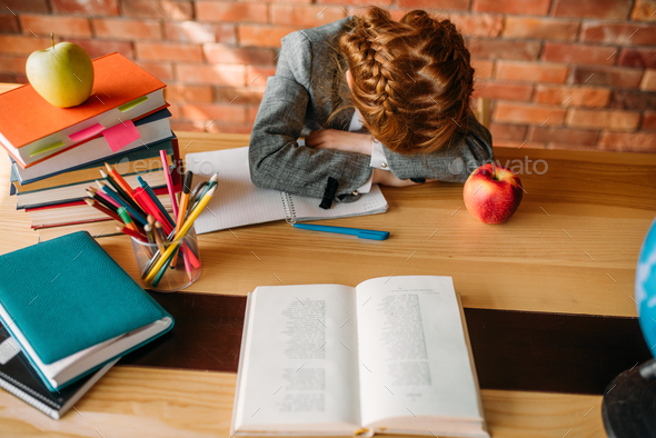 Tired schoolgirl asleep at the table in the school - Stock Photo - Images