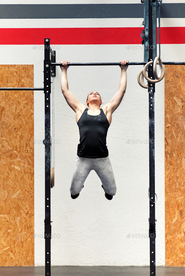 Young girl athlete doing pull-ups on a bar - Stock Photo - Images