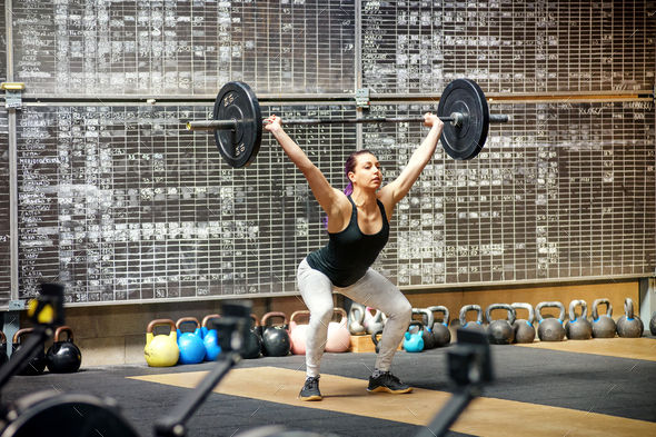 Young woman performing the snatch in a gym - Stock Photo - Images