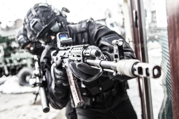 Police special reaction team member aims with gun - Stock Photo - Images