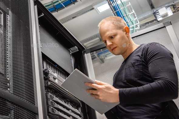 Male IT Professional Using Digital Tablet to Monitor Datacenter Status - Stock Photo - Images