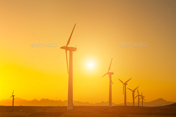 Electric wind turbines farm silhouettes on sun background - Stock Photo - Images