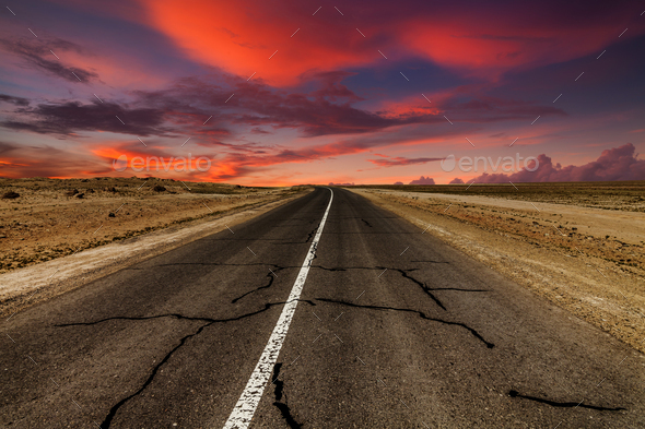 Picturesque fiery sunset over the cracked desert road - Stock Photo - Images