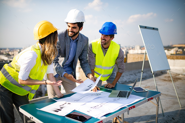 Team of architects and engineer in group on construciton site check documents and business workflow - Stock Photo - Images