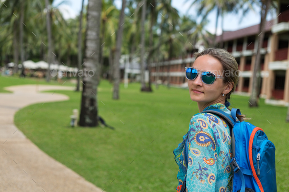 beautiful girl with blue backpack on a path with palm trees - Stock Photo - Images